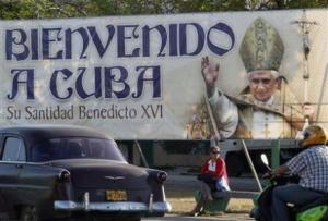 Woman sits under banner of Pope Benedict XVI in Havana